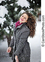 Beautiful woman enjoys the winter snow