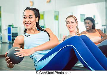 Beautiful woman exercising Russian twist with med ball for strong abs