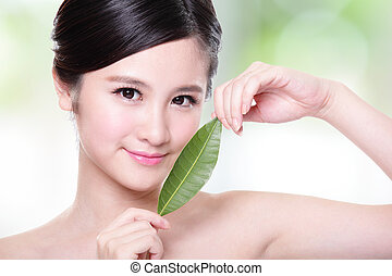 beautiful woman face portrait with green leaf