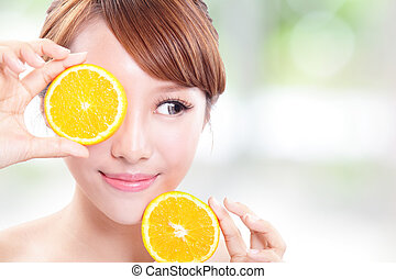 Beautiful woman face with juicy orange and look empty copy space, green background, asian beauty model