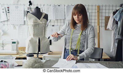 Beautiful woman fashion designer is taking photos of...