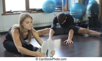 beautiful woman fitness athlete doing stretching leg muscles, a man close to her student. She trainer instructor.