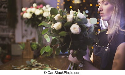 Beautiful woman florist with flowers in flowers shop -...