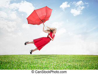 Beautiful woman flying above the grass with a broken...