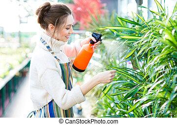 Beautiful woman gardener in colorful apron spraying flowers and plants