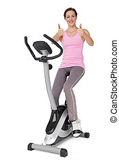 Beautiful woman gesturing thumbs up on stationary bike
