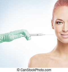 Beautiful woman gets an injection in her face over blue background