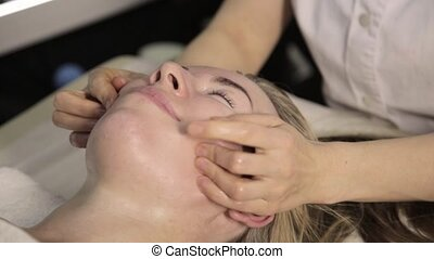 Beautiful woman getting facial massage. finger massage with...