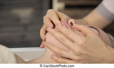 Beautiful woman getting lip massage. massage with fingers in...