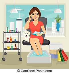 Beautiful woman getting spa pedicure procedure talking on smartphone and reading fashion magazine