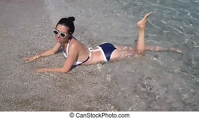 Beautiful woman getting tan in sea waves. attractive girl in sunglasses on beach vacation chill in water