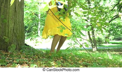 Beautiful woman girl in dress sit near tree trunk and start using laptop computer in park. 4K