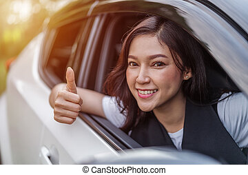 woman giving thumb up inside her car
