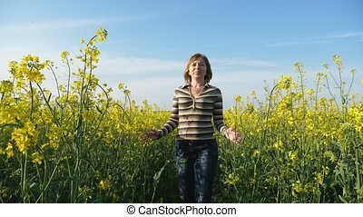 Beautiful woman going and touching rapeseed flowers in a...