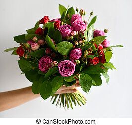 Beautiful woman hand hold bouquet of red and pink roses peony flowers on white