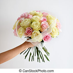 Beautiful woman hand hold bouquet of yellow and pink roses flowers on white