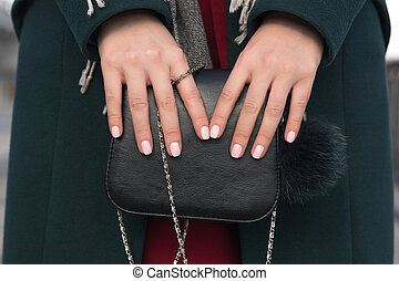 Beautiful woman hands holding black leather purse