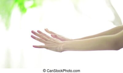 Beautiful woman hands on a blurred background of water and...