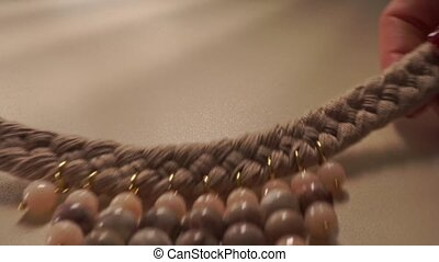 Beautiful woman hands putting beige necklace down on the table