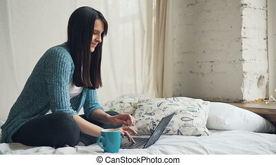 Beautiful woman happy freelancer is working at home using laptop and smiling looking at screen and enjoying freelance work. People, technology and flats concept.