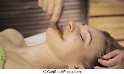 Beautiful woman has a acupressure on a face with scraper...