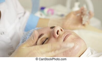 beautiful woman having cosmetic treatment at spa salon. cosmetologist in a medical gloves, touching girl's face.