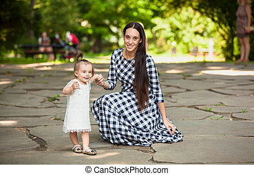 woman having fun with baby daughter at park