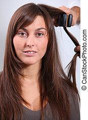 Beautiful woman having her hair dressed