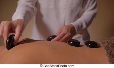 beautiful woman having hot stone massage at spa - wellness,...