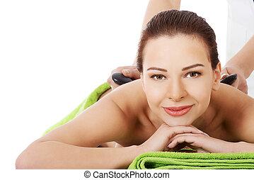Beautiful woman having stone massage.