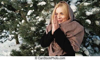 Beautiful woman heats hands, snow covered coniferous forest