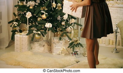 Beautiful woman hiding gifts under Christmas tree while...