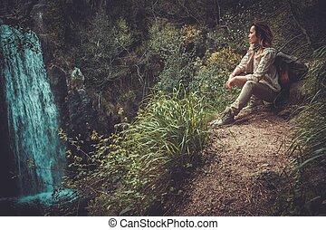 Beautiful woman hiker sitting near waterfall in deep forest.