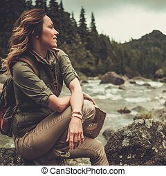 Beautiful woman hiker sitting on the stone near wild ...