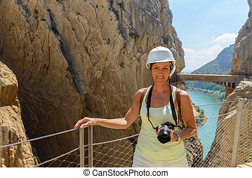 Beautiful woman hiking and holding camera in mountains at the King's little pathway in Malaga, Spain