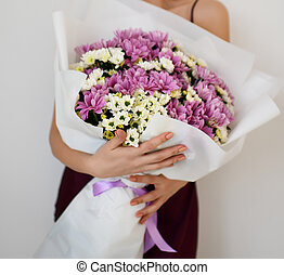 Beautiful woman hold bouquet of chrysanthemum flowers white and purple