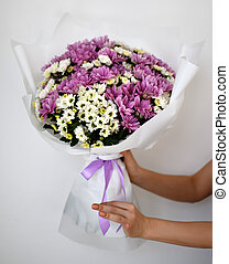 Beautiful woman hold bouquet of chrysanthemum flowers yellow and purple on white