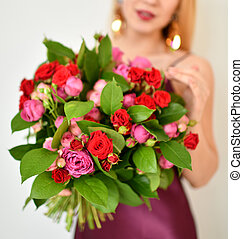 Beautiful woman hold bouquet of red and pink roses flowers happy smiling on grey