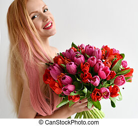 Beautiful woman hold bouquet of red and pink tulip flowers happy smiling on grey