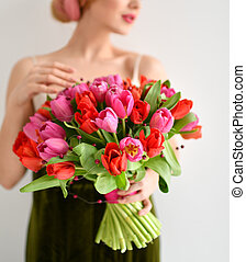 Beautiful woman hold bouquet of red pink tulips flowers on grey