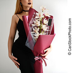 Beautiful woman hold bouquet of white pink orchid flowers on grey