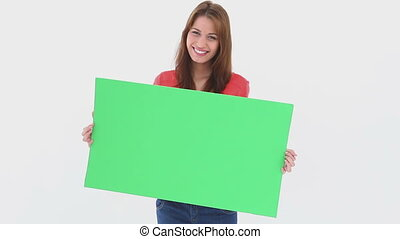 Beautiful woman holding a blank poster against white...