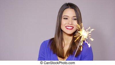Beautiful woman holding a burning sparkler