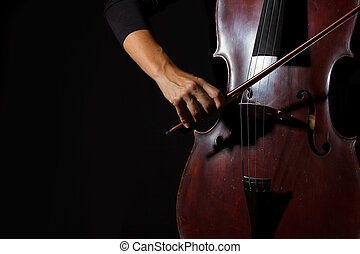 Beautiful woman holding a cello with selective light in...