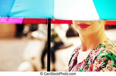 Beautiful woman holding a colorful umbrella