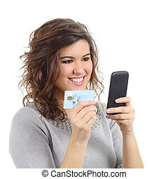Beautiful woman holding a credit card buying on the smart phone