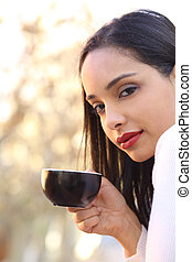 Beautiful woman holding a cup of coffee outdoor