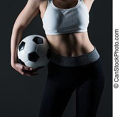 Beautiful woman holding a football gray background