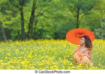 Beautiful woman holding a parasol in a meadow