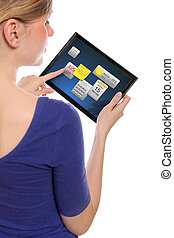 beautiful woman holding a touchpad pc, one finger touches...